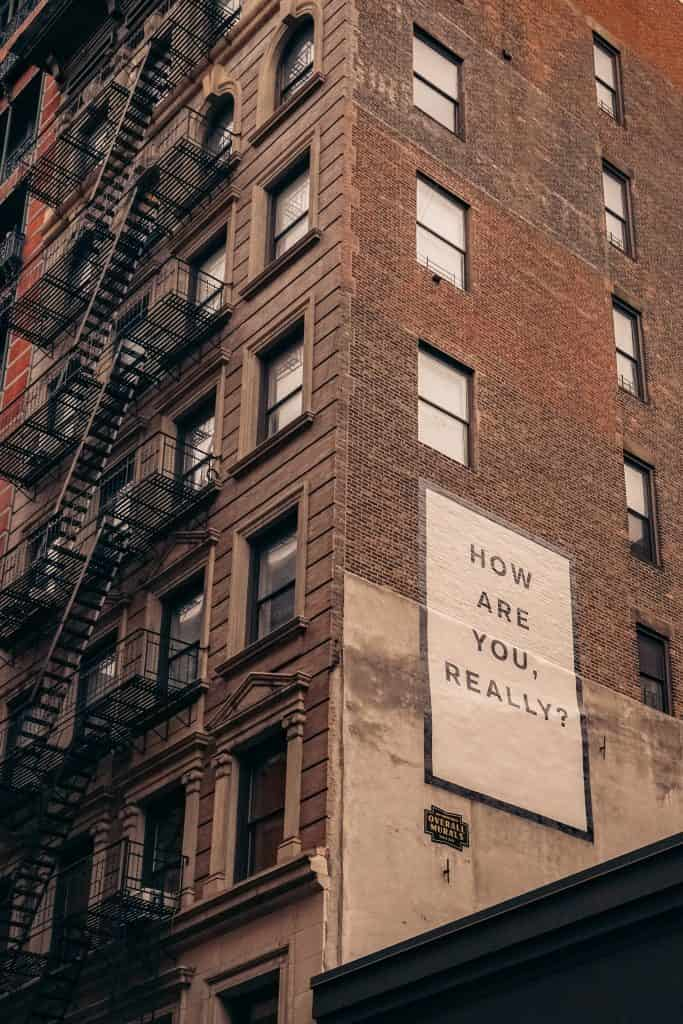 About Tom Keya - Building with a 'How Are You Really' sign